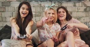 Drie tienersdames die op een PlayStation-spel voor de camera bij de partij van de sleepovernacht, in pyjama's spelen zij stock footage