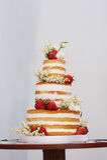 Drie-tiered huwelijkscake met aardbeien op lijst Stock Foto