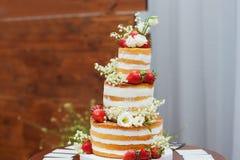 Drie-tiered huwelijkscake met aardbeien op lijst Royalty-vrije Stock Foto