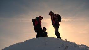 Drie toeristen met rugzakken in de winter kwamen op een heuvel in de stralen van de zon samen Klimmers bovenop een sneeuwberg stock videobeelden