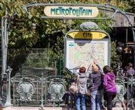 Drie toeristen richten op grote kaart van Metro van Parijs op het Cite einde Stock Foto