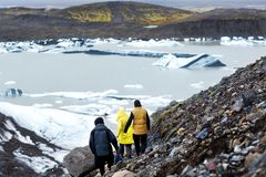 Drie toeristen zullen op een ijsberg in IJsland zijn stock fotografie