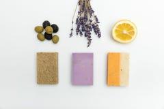 Drie types op eigengemaakte zeep met droge lavendel, olijven en citroen die op wit wordt geïsoleerd stock foto's