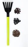 Drie types van zwarte zaden en een hark op een witte achtergrond Royalty-vrije Stock Foto