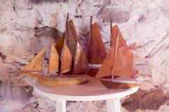 Drie uitstekende met de hand gemaakte houten zeilbootreplica's op witte rondetafel stock foto