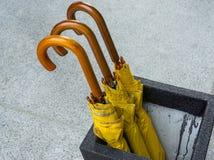 Drie van gele gevouwen paraplu's Royalty-vrije Stock Afbeeldingen