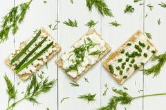 Drie vegetarisch ontbijt maakte van toost met kwark en greens op een witte houten lijst, dieet royalty-vrije stock afbeelding