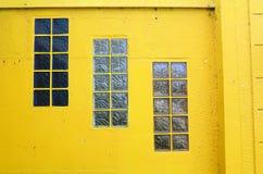 Drie vensters, gele muur stock afbeeldingen