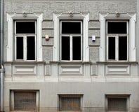 Drie vensters met decoratieve steenkaders in het gestileerde huis Stock Afbeelding