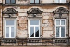Drie Vensters op de voorgevel van het oude sjofele huis stock foto