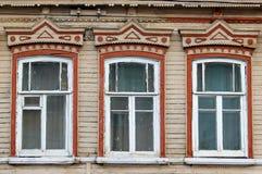 Drie vensters op een rij op een muur van een oud Russisch die huis met houtsnijwerk wordt verfraaid Royalty-vrije Stock Afbeeldingen