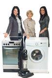 Drie verkoopvrouwen die aan huishoudapparaten tonen Stock Foto's