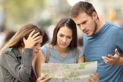 Drie verloren toeristen die een plaats in een kaart proberen te vinden stock afbeelding