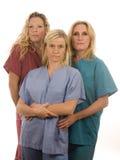 Drie verpleegsters in medisch schrobt kleren Royalty-vrije Stock Afbeelding