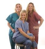 Drie verpleegsters in medisch schrobt kleren Stock Foto's