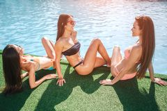Drie verrukkelijke modellen zitten op gras bij rand van zwembad Één krijgt tan van zon _ander twee kijken bij elkaar en royalty-vrije stock fotografie