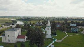 Drie verschillende kerken in het dorp en de rivier op een achtergrond - Suzdal, Rusland stock footage