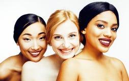 Drie verschillende natievrouw: Aziaat, Afrikaans-Amerikaan, Kaukasisch samen geïsoleerd bij het witte gelukkige glimlachen als ac stock afbeelding