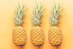 Drie verse ananassen die op oranje achtergrond liggen Hoogste mening Vlak leg concept Plaats voor tekst royalty-vrije stock foto's