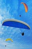 Drie vliegende valschermen Stock Foto's