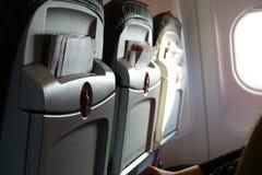 Drie vliegtuigzetels met promotiebrochures in de cabine van de vliegtuigenpassagier Licht van patrijspoort Mensen als voorzitter Stock Foto's