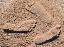 Drie voetafdrukken op bruin zand stock foto
