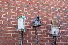 Drie vogelhuizen met baksteenachtergrond stock afbeelding