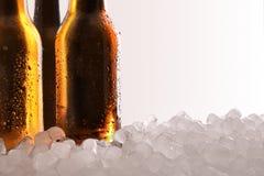 Drie volledige bierflessen op ijs en wit detail als achtergrond stock fotografie