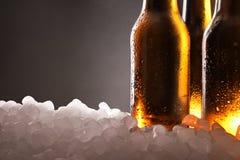 Drie volledige bierflessen op ijs en zwart detail als achtergrond royalty-vrije stock afbeeldingen