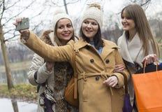 Drie volwassen meisjes fotograferen met een mobiele telefoon royalty-vrije stock afbeelding