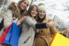 Drie volwassen meisjes fotograferen met een mobiele telefoon royalty-vrije stock fotografie