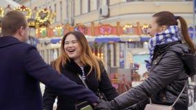 Drie volwassen mensen die holdingshanden wervelen bij slowmotion carrouselachtergrond, stock video