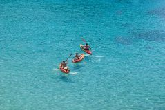 Drie volwassenen op rode kajaks in het overzees stock foto's