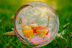 Drie vormen cake, Stuk speelgoed vliegtuig en partijsterretje in het effect van de glasbal met Greem-tuinachtergrond tot een kom Stock Afbeelding
