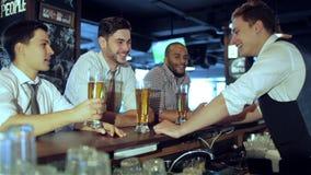 Drie vrienden die bij de bar zitten en houden het bier stock videobeelden