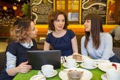Drie vrienden die in een koffie spreken die aan laptop werken en cakes eten Royalty-vrije Stock Afbeelding