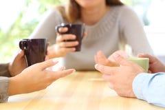 Drie vrienden die en koffiekoppen spreken houden Stock Foto's