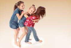 Drie vrienden die en pret spelen hebben Stock Afbeeldingen