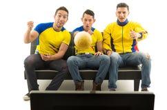 Drie vrienden die op bank zitten die gele sportenoverhemden dragen die op televisie met enthousiasme letten, gouden bal die binne stock fotografie