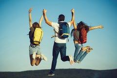 Drie vrienden die op bergbovenkant springen op blauwe hemel stock foto
