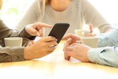 Drie vrienden die op media in een slimme telefoon letten stock fotografie