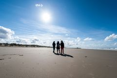 Drie vrienden die op strand in de winter lopen stock foto's