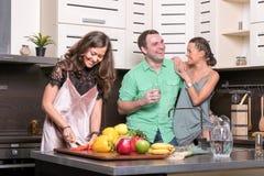 Drie vrienden die pret in de keuken hebben Stock Afbeeldingen