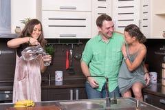Drie vrienden die pret in de keuken hebben Stock Fotografie