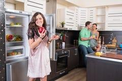Drie vrienden die pret in de keuken hebben Stock Foto's