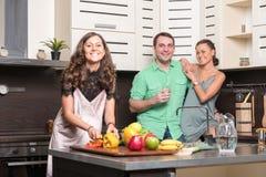 Drie vrienden die pret in de keuken hebben Royalty-vrije Stock Afbeeldingen