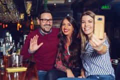 Drie vrienden die selfie in een bar nemen - Beeld royalty-vrije stock afbeeldingen