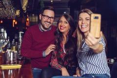 Drie vrienden die selfie in een bar nemen - Beeld stock afbeeldingen