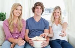Drie vrienden die van popcorn samen genieten Stock Foto