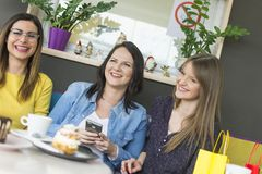 Drie vrienden in een cake winkelen stock afbeeldingen